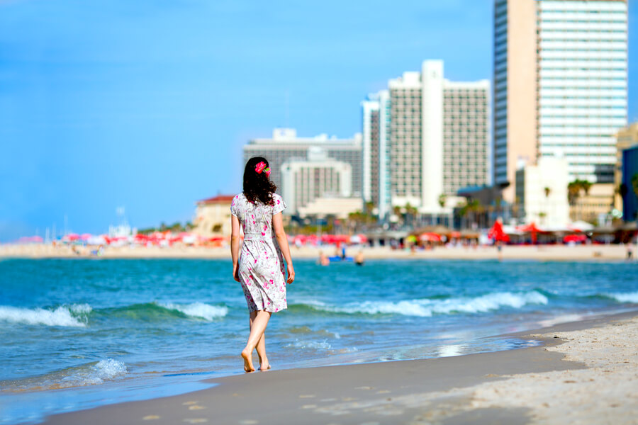 Young Woman Walking on the Beach in Tel-Aviv, Israel.