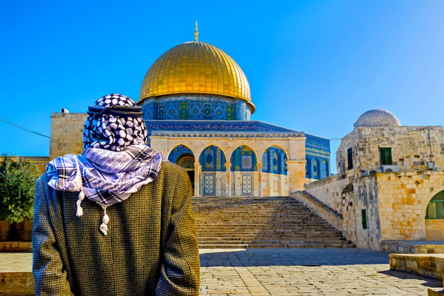 The pensive Palestinian in keffiyeh stands in shade of the Chain Gates, and look at the Dome of the Rock, Jerusalem, Israel.